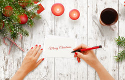 Woman write Christmas greeting message on paper. Top view of white wooden table with christmas tree, decorations, candle, tea, gift royalty free stock photos