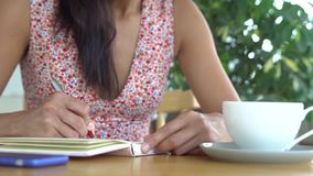 Woman write in diary. Smartphone and cup of coffee on the table royalty free stock image