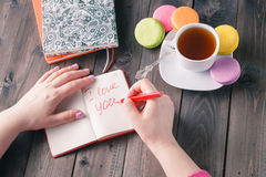 Woman write letter i love you while drinking coffee Royalty Free Stock Images