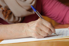 Woman write a letter. Pen in the hands of an elderly woman and a sheet of paper Royalty Free Stock Photo