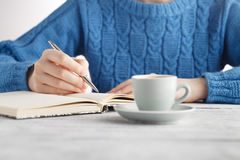 Woman write in notebook and drink coffee Stock Image