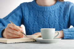 Woman write in notebook and drink coffee Stock Photography
