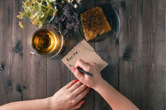 Woman write recipe of medicinal herbs om table Royalty Free Stock Photography