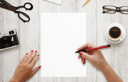 Woman write with red pen on , white paper. stock photo