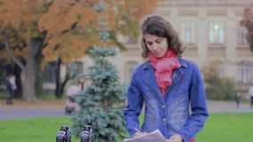 Woman writer takes notes on paper in the park