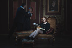 Woman writer writing a novel. A book about an old tyrant and a young girl royalty free stock images