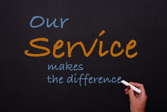 Woman writes on blackboard our service makes the difference.  Royalty Free Stock Photos