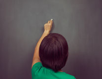 Woman writes on the blackboard Royalty Free Stock Photography
