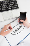 Woman writes a business plan with your phone and laptop Stock Photography