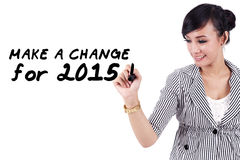 Woman writes a change for 2015. Young asian woman writes a text to make a change in 2015 Royalty Free Stock Image