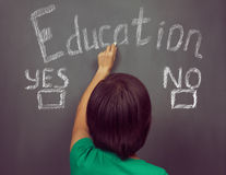 Woman writes choice education. Unrecognizable woman writes choice education on the blackboard, concept of education Stock Images