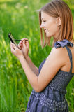 Woman writes in communicator. Young attractive woman writes in communicator with help stylus, on green background of summer city park stock photos