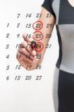 Woman writes the days on the calendar Stock Photos