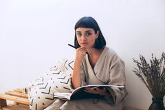 Woman writes in diary notebook. Thoughtful and peaceful calm woman holds pencil or pen in hand, deep in her thoughts over open book or diary, in cosy home Royalty Free Stock Images