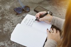 Woman Writes Down Her Life Goals in a Journal with Sunglasses and a Phone on a Table. Young female writes her life goals with a pen and paper. Sunglasses and stock photo