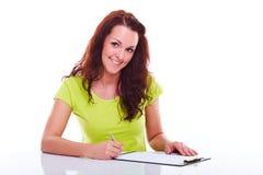 Woman writes on the folder Royalty Free Stock Photos