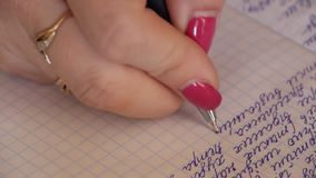A woman writes handwritten text with a ballpoint pen in a notebook. A notebook in a cell stock footage