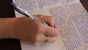A woman writes handwritten text with a ballpoint pen in a notebook. A notebook in a cell stock video footage