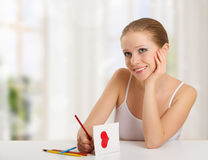 Woman writes love letter - card for valentines day. Beautiful young woman writes a love letter - a card for valentines day in the room royalty free stock photo