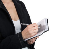 The woman writes in a notebook. The woman writes something in a notebook having control over it on a white background Stock Image