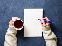 Woman writes in notebook on dark blue table, hand in shirt holding a pencil, cup of tea, sketchbook drawing, top view. Woman writes in notebook on a dark blue royalty free stock images