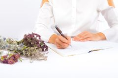 A woman writes in a notebook. Medicinal herbs stock photography