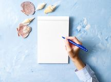 woman writes in notebook on stone blue table, Mock up with frame of seashell, top view, planning holiday by sea royalty free stock photos