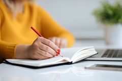 Woman writes notes on a diary. Woman writes notes on a black diary in the office Stock Photo