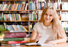 Woman writes notes in the library Royalty Free Stock Photo