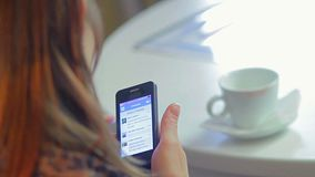 Woman writes sms types mobile phone message in cafe conversation. Stock footage stock video