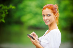 Woman writes stylus on screen of device. Carroty beautiful woman writes stylus on screen of your device, on green park summer Stock Images