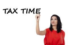 Woman writes tax time on whiteboard Stock Photo
