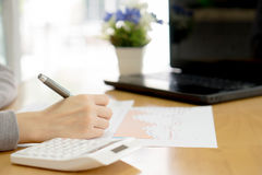 Woman writes a text message on paper and laptop,calculator Stock Image