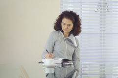 Woman writing. Woman sitting at a glass table writing in her journal Royalty Free Stock Photography