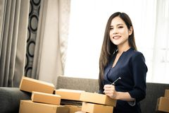 Woman writing address send package for online business. Woman writing address and send package for online business Royalty Free Stock Image