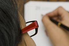 Woman writing on agenda. Wearing red glasses stock images