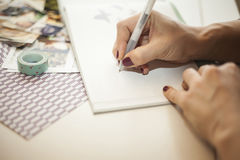 Woman writing in a baby book Royalty Free Stock Photography
