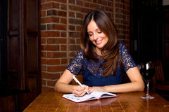 Woman writing in a bar Royalty Free Stock Photography