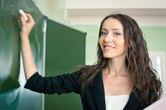 Woman writing on blackboard at classroom Stock Images