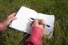 Woman writing in a blank book. Woman lying in the grass and writing in a blank book Royalty Free Stock Photo