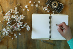 Woman writing on blank notebook next to spring white cherry blossoms tree on vintage wooden table. Royalty Free Stock Photos