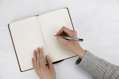 Woman writing in a blank open diary or journal. Woman writing in a blank open diary, notebook or journal with a ballpoint pen in a communications and business royalty free stock photo