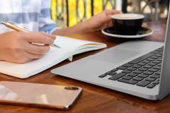 Woman writing blog content in notebook at table
