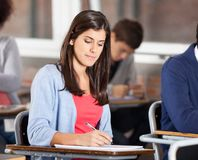 Woman Writing On Book At Desk In Classroom Royalty Free Stock Photo