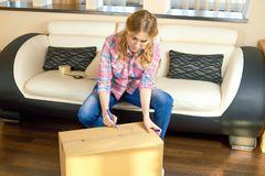 Woman writing on box, relocation. Royalty Free Stock Images