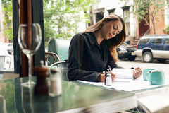Woman Writing At Cafe Stock Images