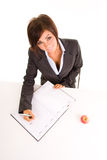 Woman writing in calendar. Woman in business attire writing in her schedule.  Isolated against a white background Stock Images