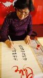Woman writing calligraphy Stock Image