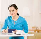 Woman writing check from checkbook. To pay monthly bills royalty free stock images