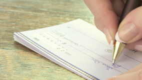 Woman writing a check stock footage